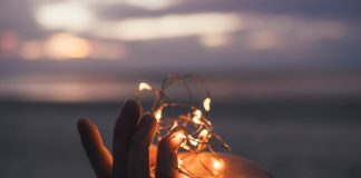 Hand holding led lights. Ocean in the sunset background.