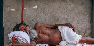 A older gray bearded man sleeping during daytime