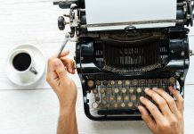 Person hands. Writing a 420 article on a old typewriter