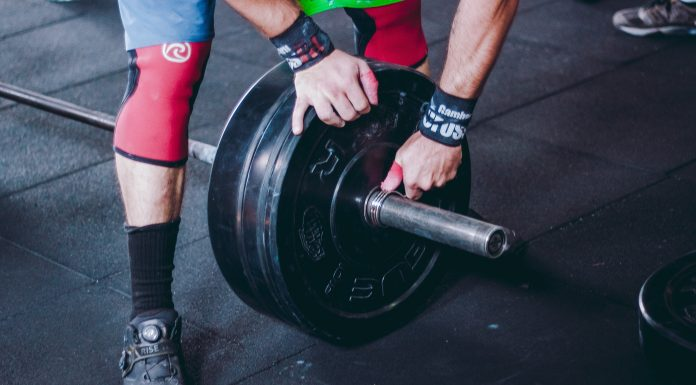 Person putting on free weight plates on a free weight bar