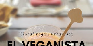 Pinkish orange smoothie in a latte glass with a wooden swizzle stick in it. In the foreground the text global vegan urbanista El Veganista.