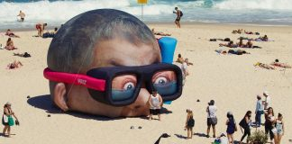 A beach with people and an oversized inflated head that makes the whole picture seem surreal.