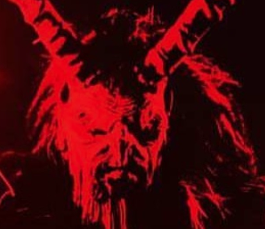 Black and red monochrome chest and up picture of a devil like man with horns